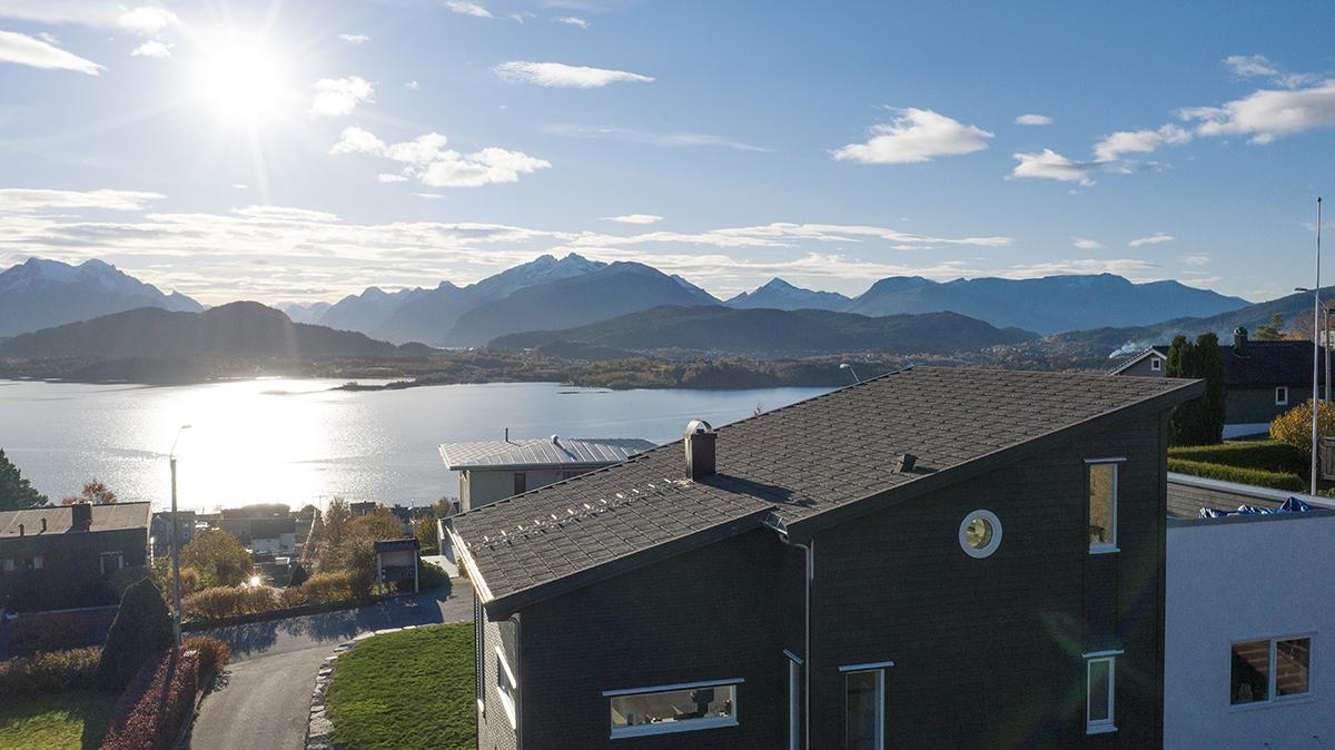 Hus med AeroDek-tak som skuer over fjell og fjord.