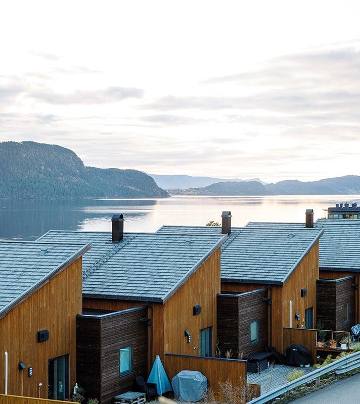 Flere hus på rekke med AeroDek-tak og utsikt over fjell og fjord.
